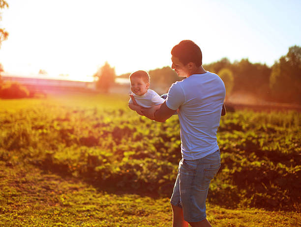 Happy father child son having fun over sunny evening sunset stock photo