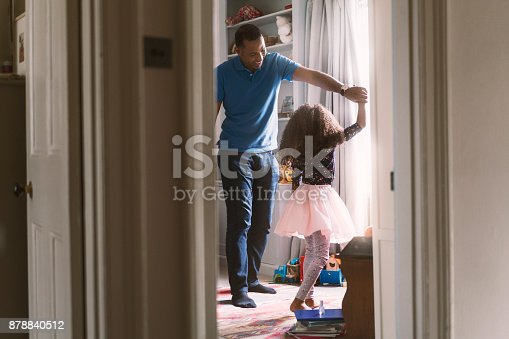 Happy father and girl dancing in bedroom. Cheerful man and daughter are enjoying at home. They are spending leisure time.