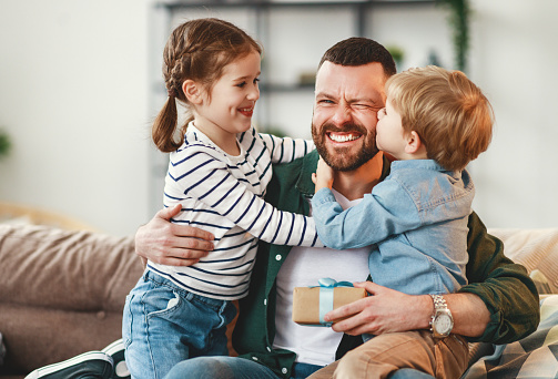 Joyful man with gift box in hand sitting on sofa at home and hugging cheerful son and daughter giving congratulations on fathers day