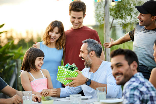 Happy father giving gift to daughter in backyard Cheerful father giving gift to daughter. Males and females are celebrating birthday in backyard. They are at table. group of friends giving gifts to the birthday girl stock pictures, royalty-free photos & images