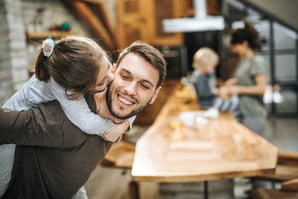 Happy father having fun while piggybacking his daughter at home. Carefree father having fun while piggybacking his small girl at home while she is kissing him. There are people in the background. little girl kissing dad on cheek stock pictures, royalty-free photos & images