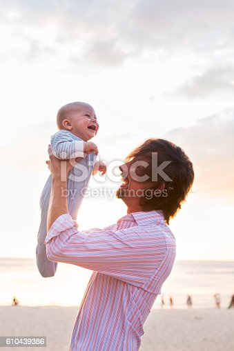 istock Happy father having fun with baby son at the beach. 610439386