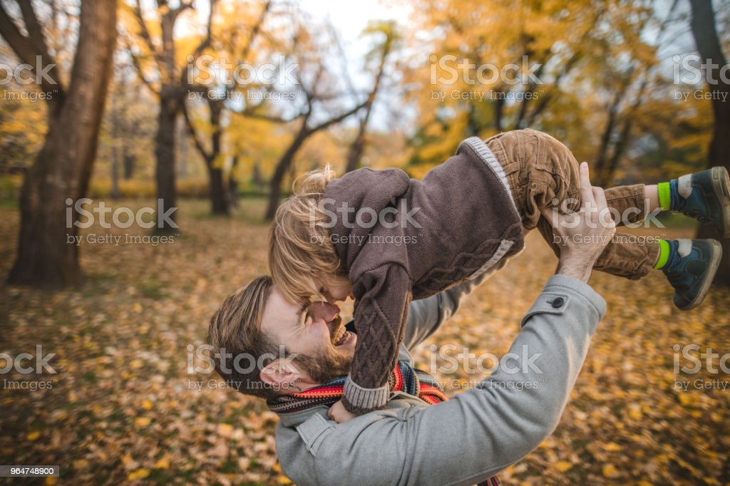Happy father having fun with his little boy in autumn day. royalty-free stock photo