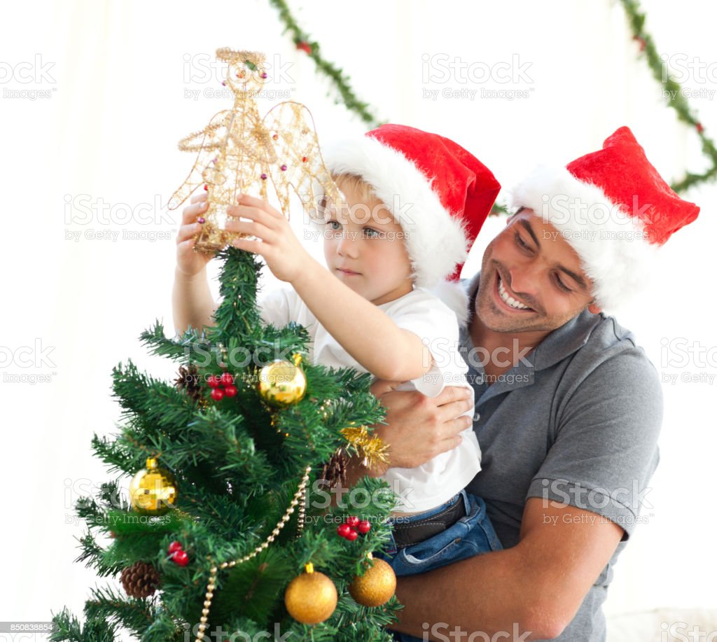 Happy father helping his son to put an angel on the Christmas tree stock photo