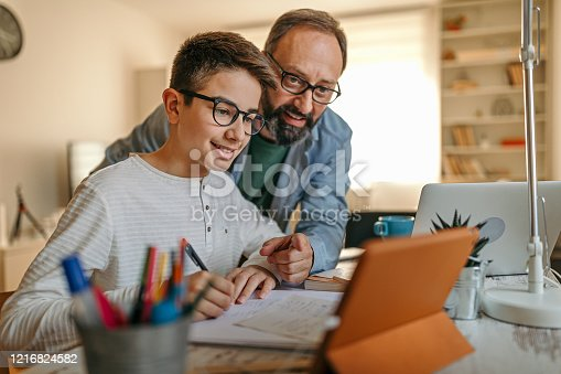 Father embracing son from behind while helping him with homework