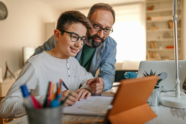 Happy father helping son with homework Father embracing son from behind while helping him with homework parent stock pictures, royalty-free photos & images