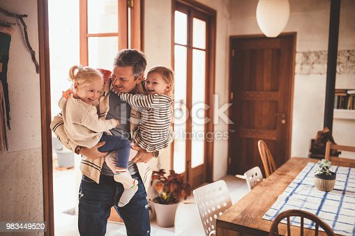 Loving father holding and embracing little cheerful daughters after returning home from work