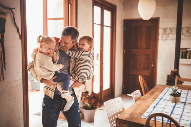 happy father holding little daughters in his arms at home - arrival stock photos and pictures