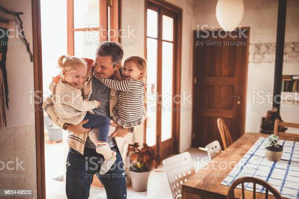 Happy father holding little daughters in his arms at home