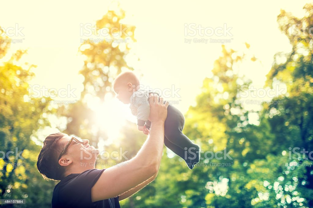 happy father holding little kid, throwing baby in air stock photo