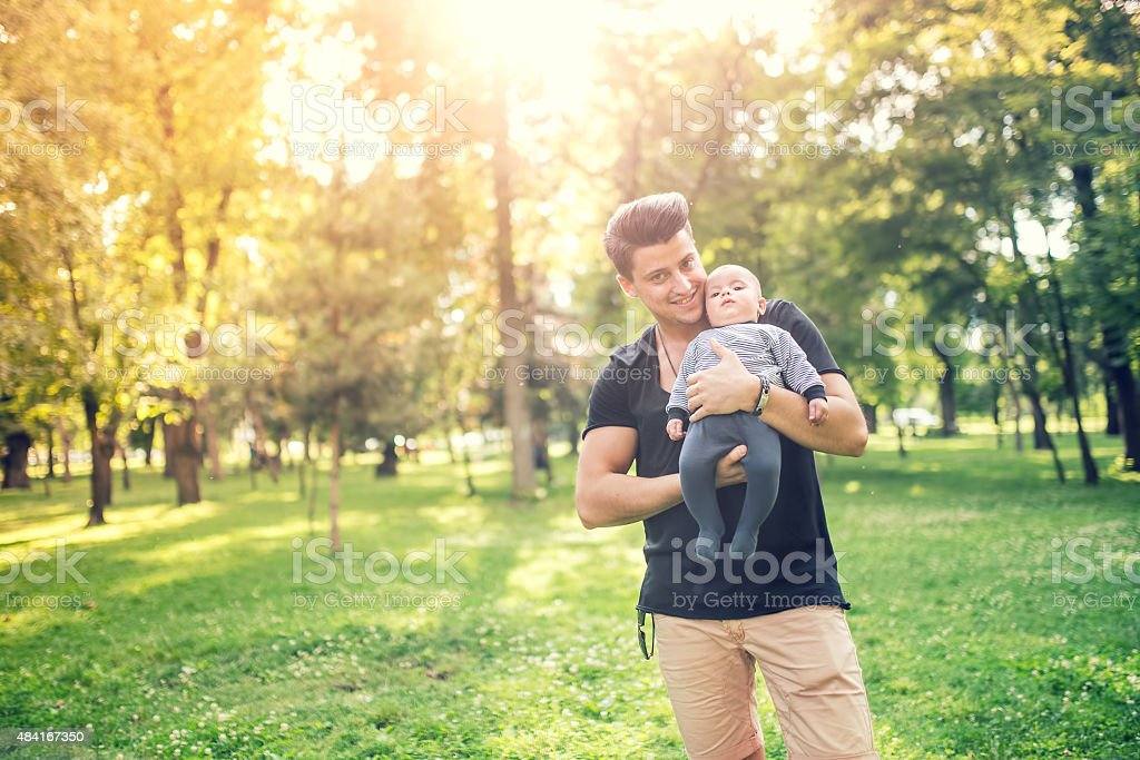 Happy father holding little son, infant boy stock photo