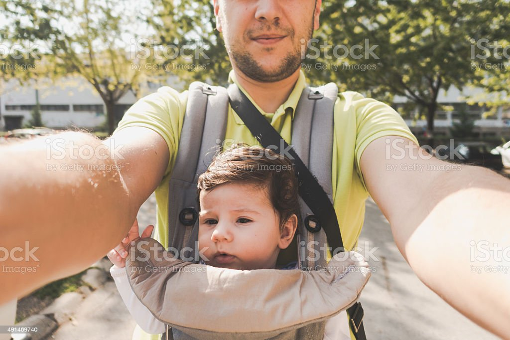 Happy father holds his baby boy in a baby carrier stock photo