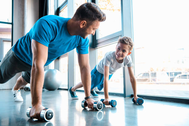 happy father looking at cheerful son and exercising with dumbbells stock photo