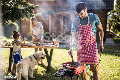 istock Happy father making barbecue for his family in the backyard. 1159752608