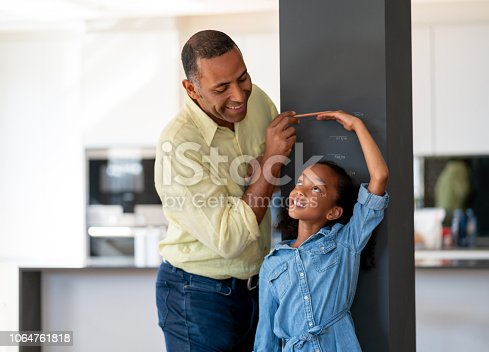 Portrait of a happy father measuring his daughter against the wall at home – parenting concepts