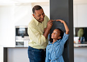 istock Happy father measuring his daughter at home 1064761818