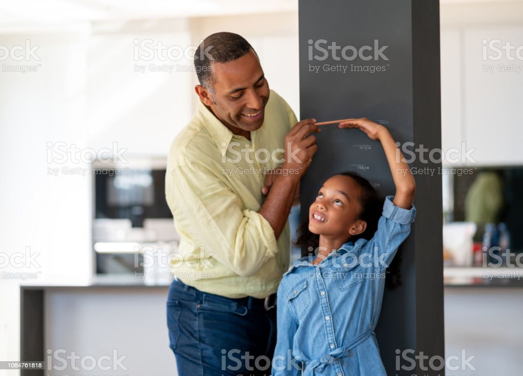 Happy father measuring his daughter at home stock photo