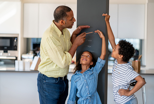 Portrait of a happy father measuring his kids at home against the wall– parenting concepts