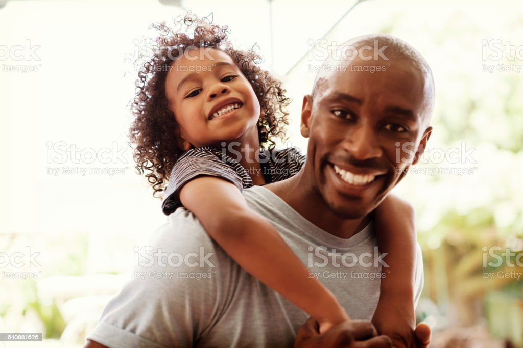 Happy father piggybacking son at yard stock photo