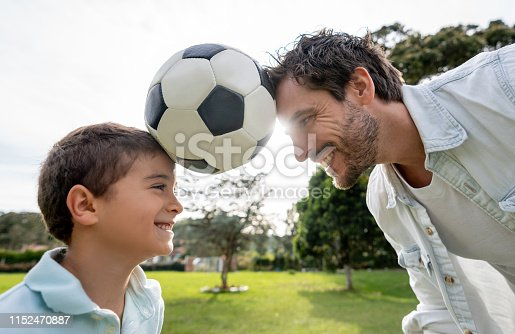 istock Happy father playing football with his son at the park 1152470887