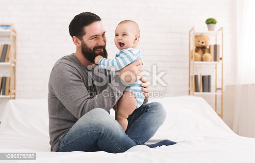 istock Happy father playing with little baby boy at home 1086875282