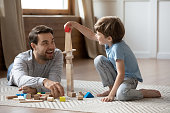 istock Happy father playing with small schoolboy in living room. 1206859187