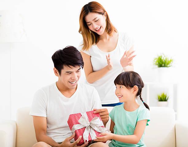 happy father receiving gift box from wife and daughter - geburtstagsgeschenk für papa stock-fotos und bilder