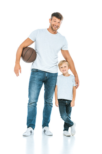 happy father standing with son while holding basketball on white