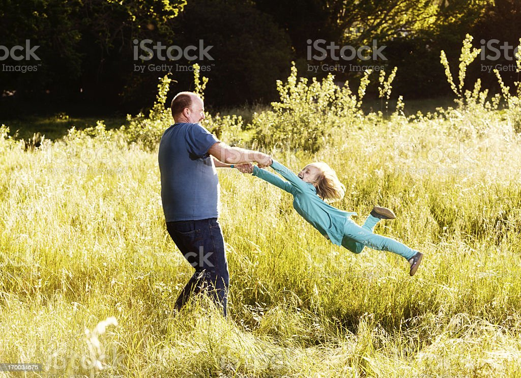 Happy father swings smiling daughter round in grassy meadow stock photo