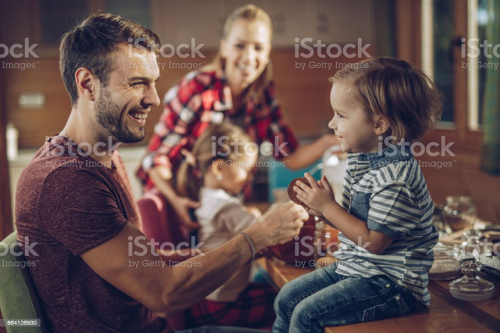 Happy father talking to his small son in dining room. royalty-free stock photo