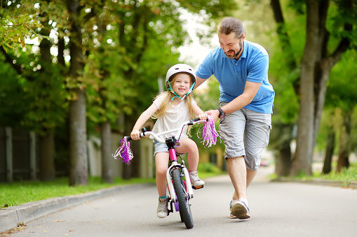 istock Happy father teaching his little daughter to ride a bicycle. Child learning to ride a bike. 938635616