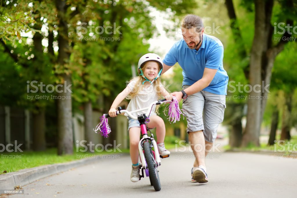 Happy father teaching his little daughter to ride a bicycle. Child learning to ride a bike. stock photo