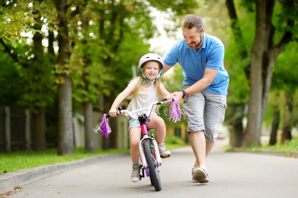 happy father teaching his little daughter to ride a bicycle. child learning to ride a bike. - cycling stock photos and pictures