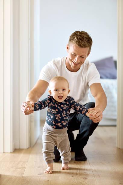 Glücklicher Vater lehrt Sohn zu Hause zu gehen – Foto