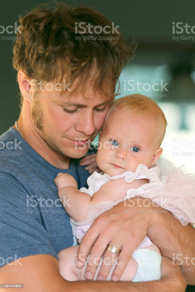 Happy Father Tenderly Hugging Baby Daughter stock photo