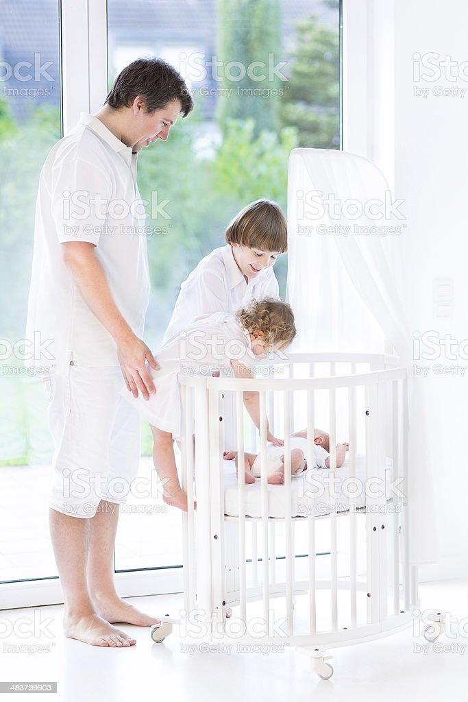 Happy father with children next round crib watching newborn baby royalty-free stock photo
