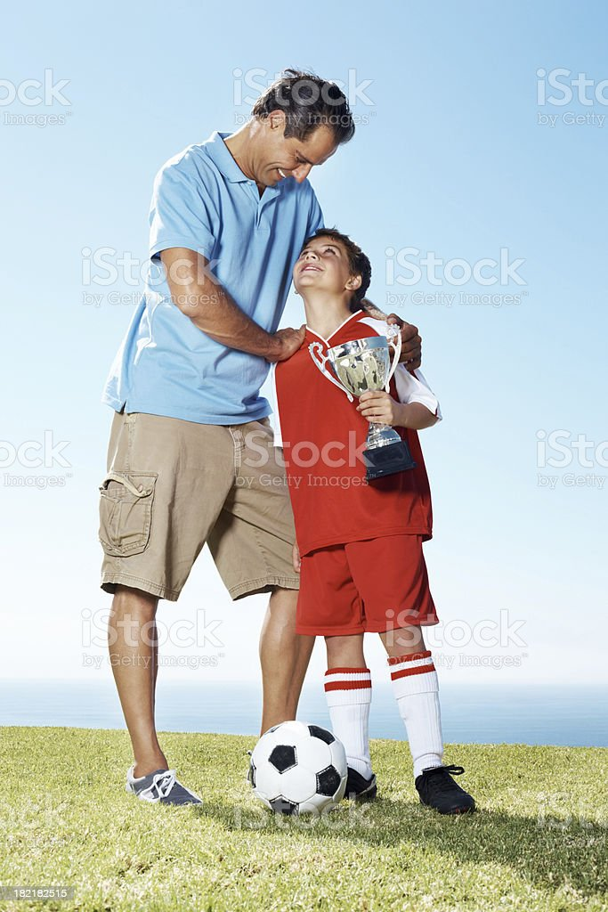 Happy father with his son holding a winners trophy stock photo