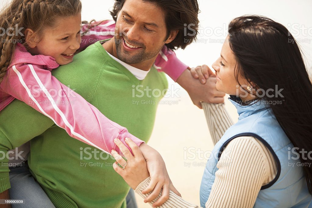 Happy father with his wife and daughter on the beach. royalty-free stock photo