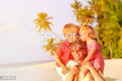 505122600 istock photo happy father with kids on shoulders having fun at beach 486685362