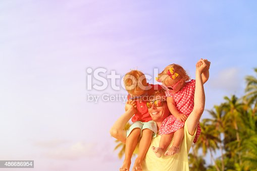 505122600 istock photo happy father with kids on shoulders having fun at beach 486686954