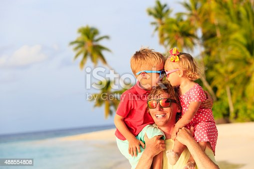 505122600 istock photo happy father with kids on shoulders having fun at beach 488554808
