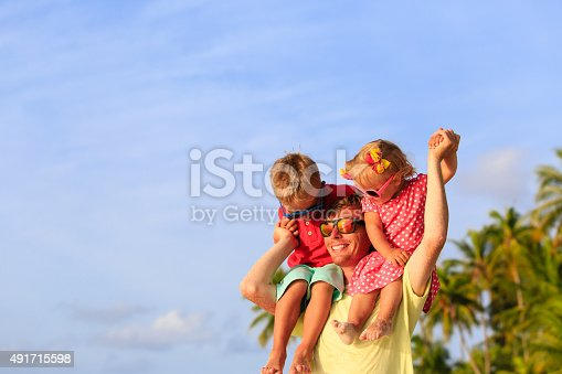 505122600 istock photo happy father with two kids on shoulders at beach 491715598