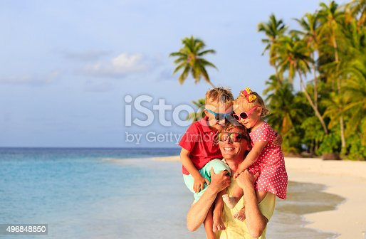 505122600 istock photo happy father with two kids on shoulders at beach 496848850