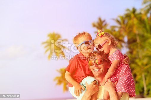 505122600 istock photo happy father with two kids on shoulders at beach 507248728