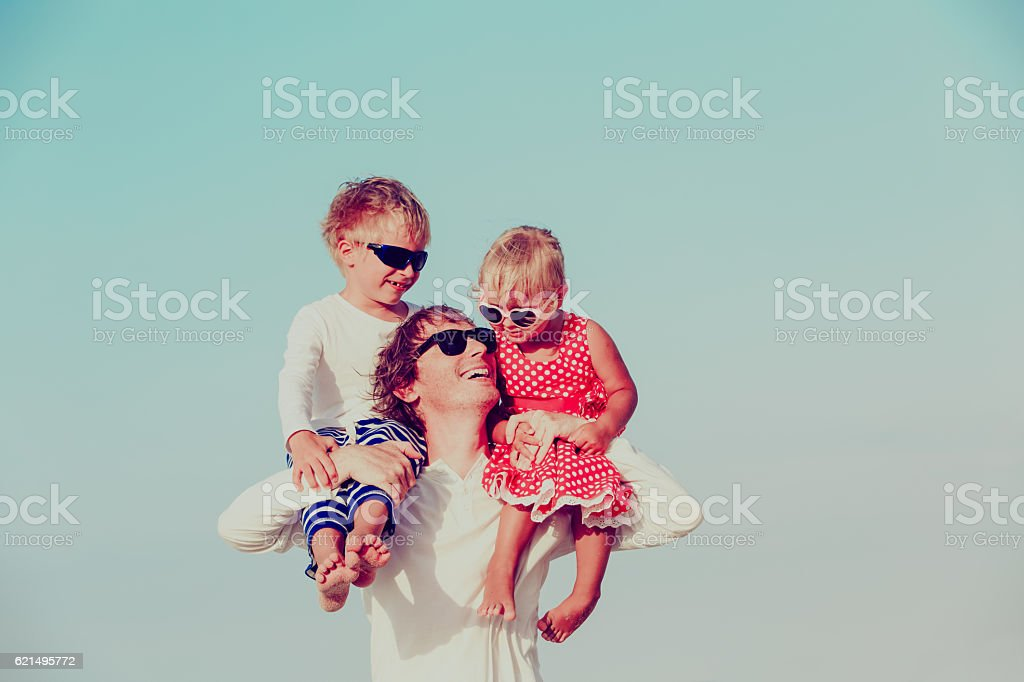 happy father with two kids on shoulders at sky foto stock royalty-free