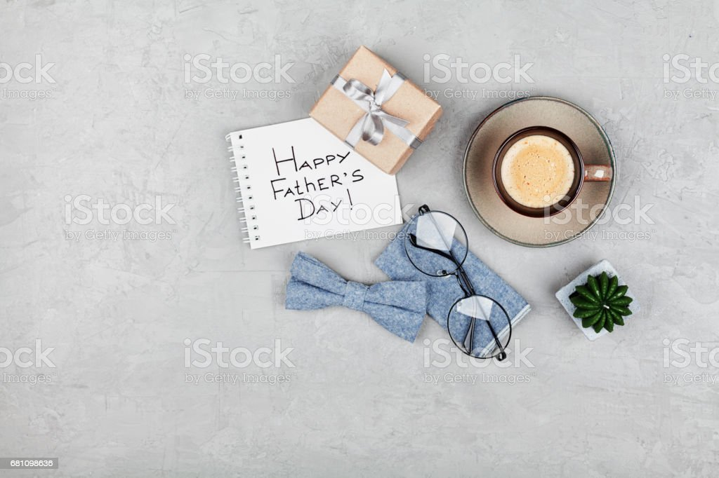 Happy Fathers Day background. Coffee cup, gift, glasses and bowtie. Flat lay. Copy space for design. stock photo