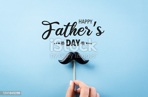 Happy Father's Day background concept with hand holding black mustache on bright blue blackground.