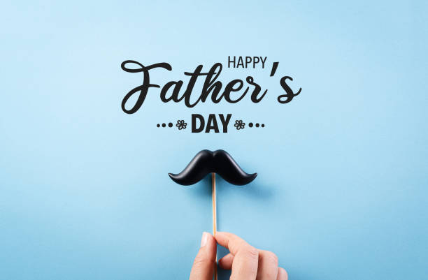 Happy Father's Day background concept with hand holding black mustache on bright blue blackground. Happy Father's Day background concept with hand holding black mustache on bright blue blackground. fathers day stock pictures, royalty-free photos & images