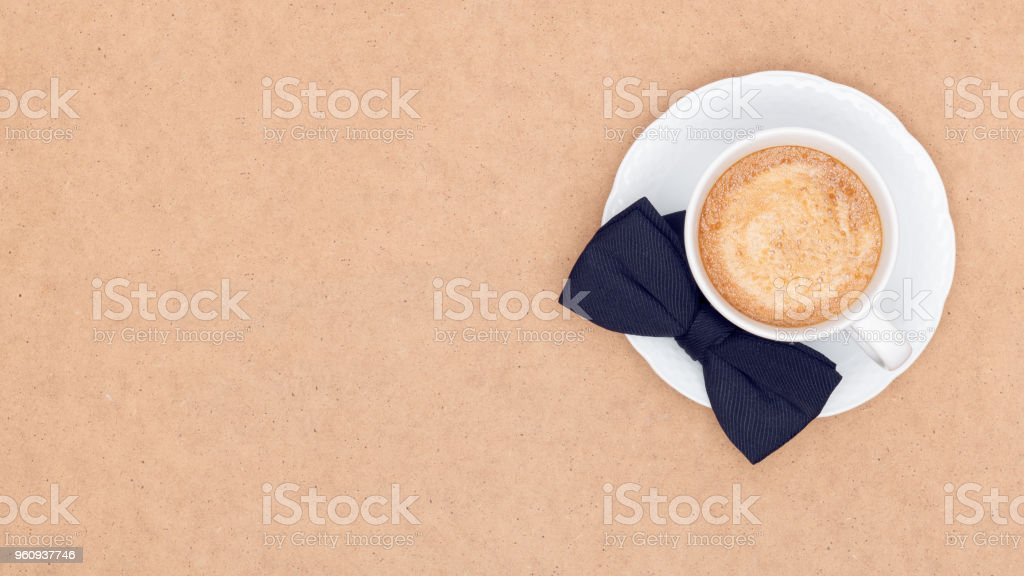 Happy Father's Day Background. Cup of coffee and black bow tie on brown background flat lay. Fathers day still life. stock photo