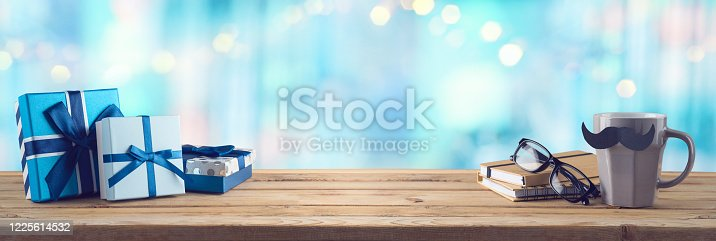 Happy Fathers day background with coffee cup, mustache and gift box on wooden table